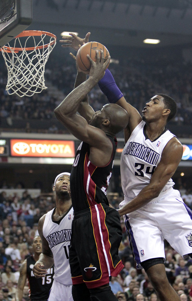 Photo - Sacramento Kings forward Jason Thompson, right, blocks a shot by Miami Heat center Joel Anthony during the first quarter of an NBA basketball game in Sacramento, Calif., Saturday, Jan. 12, 2013. (AP Photo/Rich Pedroncelli)
