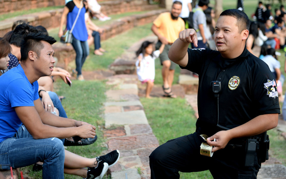 Photo -  Oklahoma County sheriff's deputy Tom Ly hands out stickers to patrons of the Moon Festival in September at Will Rogers Park in Oklahoma City. [Photos by Jackie Dobson, For The Oklahoman]