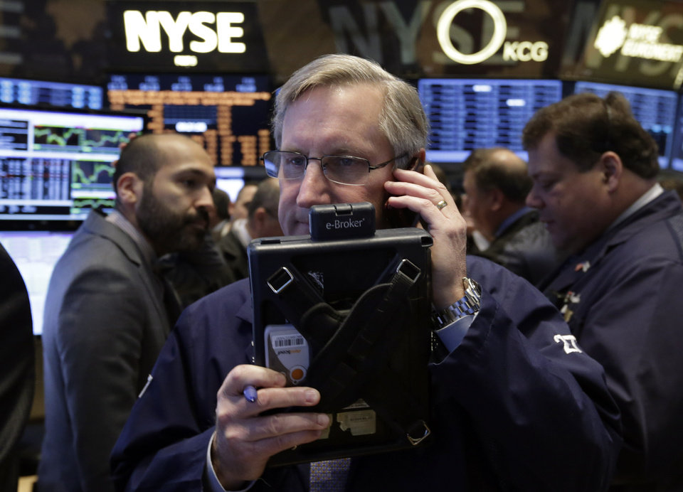 Photo - Trader Christopher Fuchs, center, works on the floor of the New York Stock Exchange Friday, Jan. 31, 2014. Stocks fell sharply in early trading Friday, as investors fretted over disappointing earnings from companies like Amazon.com and more trouble in overseas markets. (AP Photo/Richard Drew)
