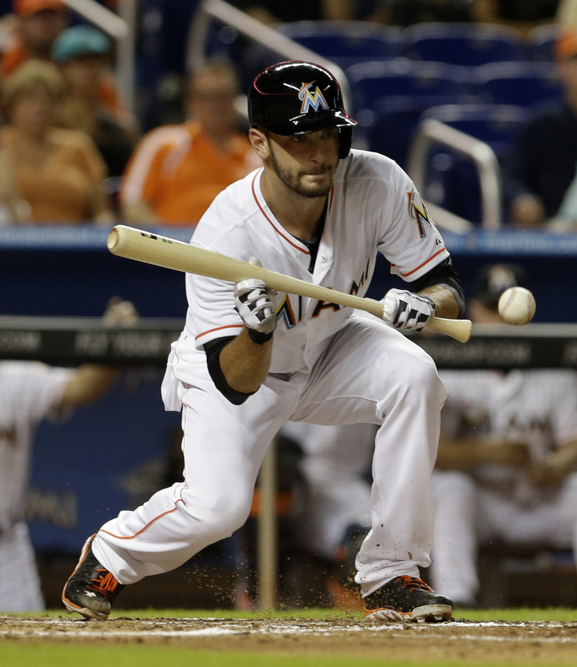 Photo - Miami Marlins' Jarred Cosart sacrifice bunts against the Cincinnati Reds in the fifth inning of a baseball game in Miami, Friday, Aug. 1, 2014. Adeiny Hechavarria was safe at second base. (AP Photo/Alan Diaz)
