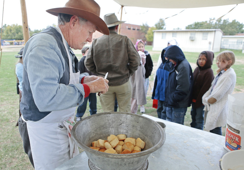Photo - Lynn Shackelford, with the Oklahoma History Center, prepares biscuits for students Friday at Lincoln Elementary School in Norman. The center's workers prepared biscuits for the students for the culmination of a weeklong study of pioneer history. Photos by David McDaniel, The Oklahoman
