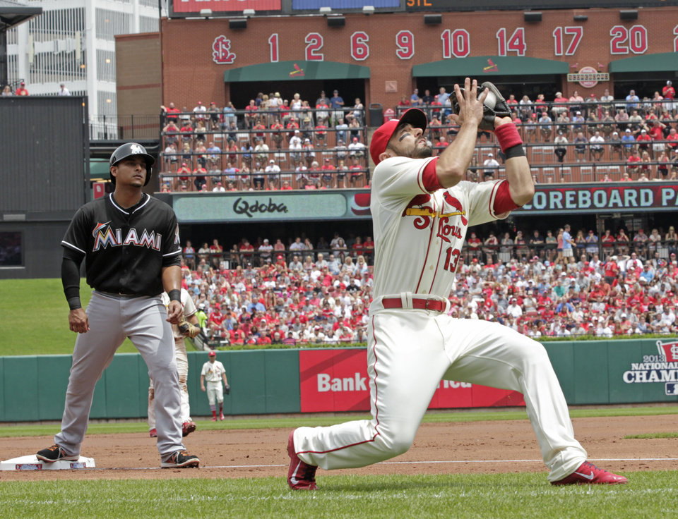 Photo - St. Louis Cardinals third baseman Matt Carpenter (13) makes a catch on a ball popped up by Miami Marlins' Garrett Jones, as Miami Marlins' Donovan Solano looks on from third base, in the first inning of a baseball game, Saturday, July 5, 2014 in St. Louis.(AP Photo/Tom Gannam)