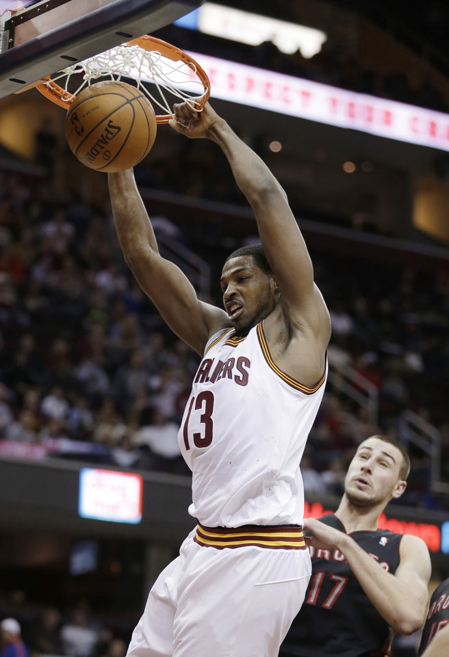 Cleveland Cavaliers' Tristan Thompson (13) dunks in front of Toronto Raptors' Jonas Valanciunas (17) during the second quarter of an NBA basketball game Wednesday, Feb. 27, 2013, in Cleveland. (AP Photo/Tony Dejak)