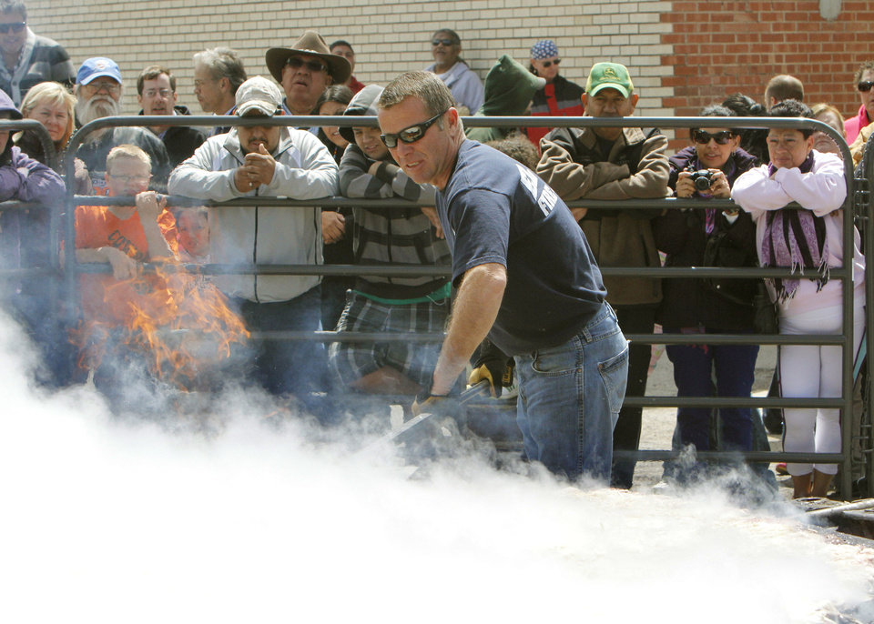 El Reno Fire Chief Kent Lagaly pats down a 750-pound burger during the  Burger Day Festival.  Photo by Paul Hellstern, The Oklahoman <strong>PAUL HELLSTERN - Oklahoman</strong>