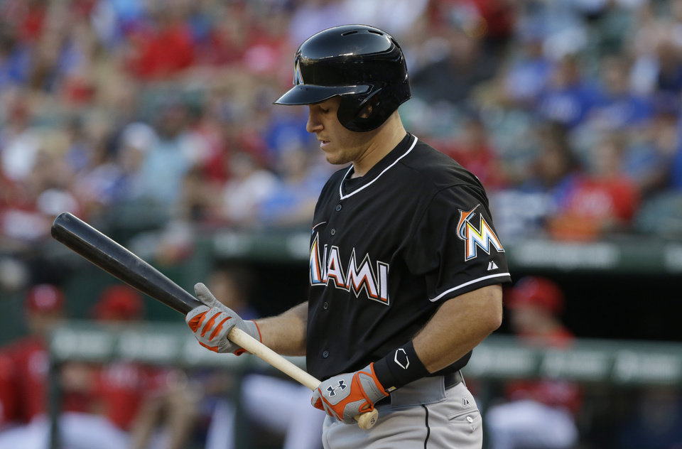 Photo - Miami Marlins Justin Bour heads back to the dugout after striking out during the second inning of a baseball game against the Texas Rangers in Arlington, Texas, Wednesday, June 11, 2014. The Rangers won 6-0.  (AP Photo/LM Otero)