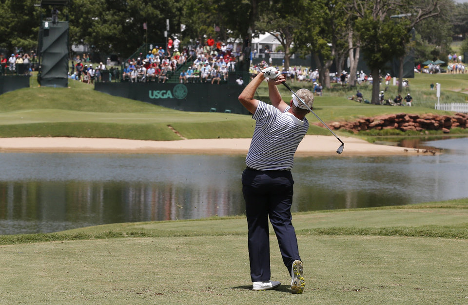 Photo - Colin Montgomerie watches his shot from the eighth tee during the third round of play at the 2014 U.S. Senior Open golf tournament at Oak Tree National in Edmond, Okla., Saturday, July 12, 2014. (AP Photo/Sue Ogrocki)