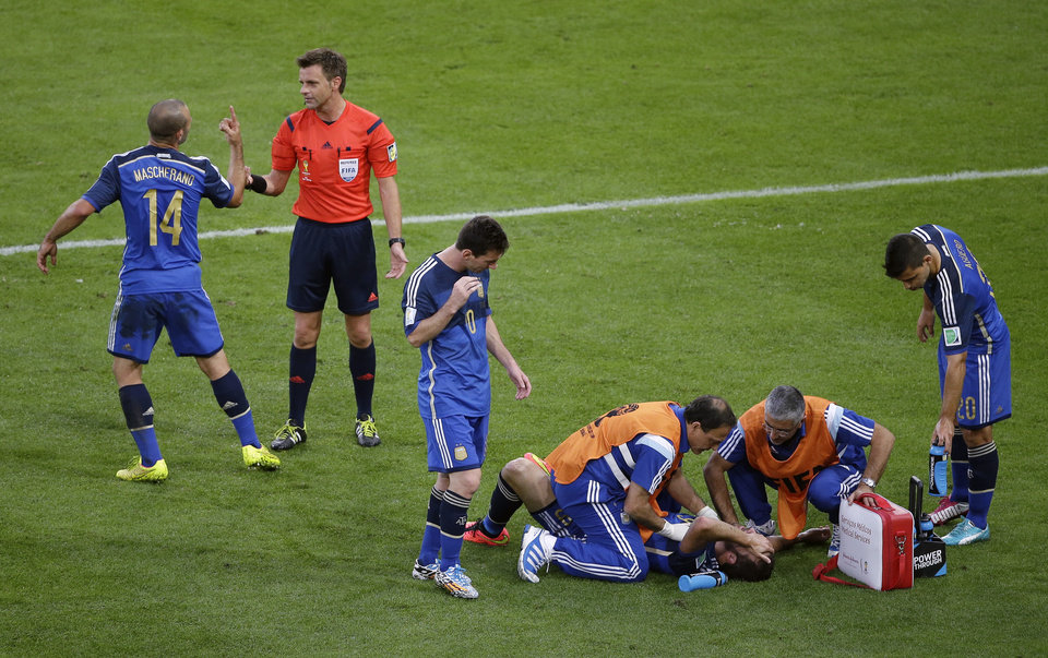 Photo - Argentina's Javier Mascherano, left, talks to  Italian referee Nicola Rizzoli as Argentina's Gonzalo Higuain receives assistance during the World Cup final soccer match between Germany and Argentina at the Maracana Stadium in Rio de Janeiro, Brazil, Sunday, July 13, 2014. Third from left Argentina's Lionel Messi. At right Argentina's Sergio Aguero.(AP Photo/Themba Hadebe)