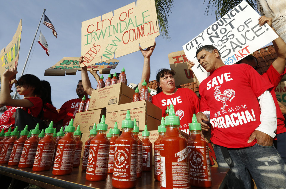 Photo - Sriracha hot sauce workers protest ahead of the city council meeting in Irwindale, Calif., Wednesday, April 23, 2014. The Irwindale City Council has declared that the factory that produces the popular Sriracha hot sauce is a public nuisance. (AP Photo/Damian Dovarganes)