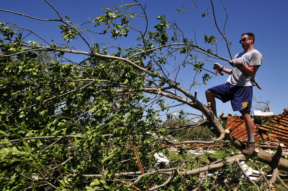 Photo - Josh Hill, a volunteer with Grace Chapel in Englewood, Colo., helps to clear downed branches from Angela and Wade Burleson's yard in El Reno Okla. on Saturday June 1, 2013 after their home was destroyed by one of the tornados that swept through Central Okla. on Friday. (AP Photo/Nick Oxford)