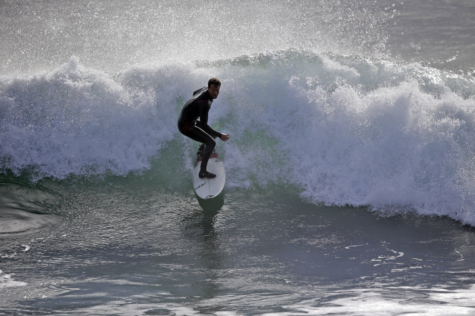 Photo - A surfer rides a wave off Steamer's Lane, a popular surf spot, Thursday, Dec. 10, 2015, in Santa Cruz , Calif.  A storm system is expected this afternoon, bringing rain to the Bay Area. (AP Photo/Marcio Jose Sanchez)