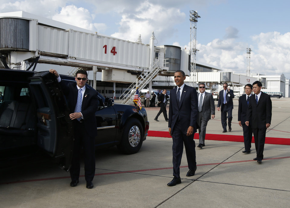 Photo -   U.S. President Barack Obama, center, walks to his motorcade vehicle as he arrives on Air Force One at Don Mueang International Airport in Bangkok, Thailand, Sunday, Nov. 18, 2012. (AP Photo/Carolyn Kaster)
