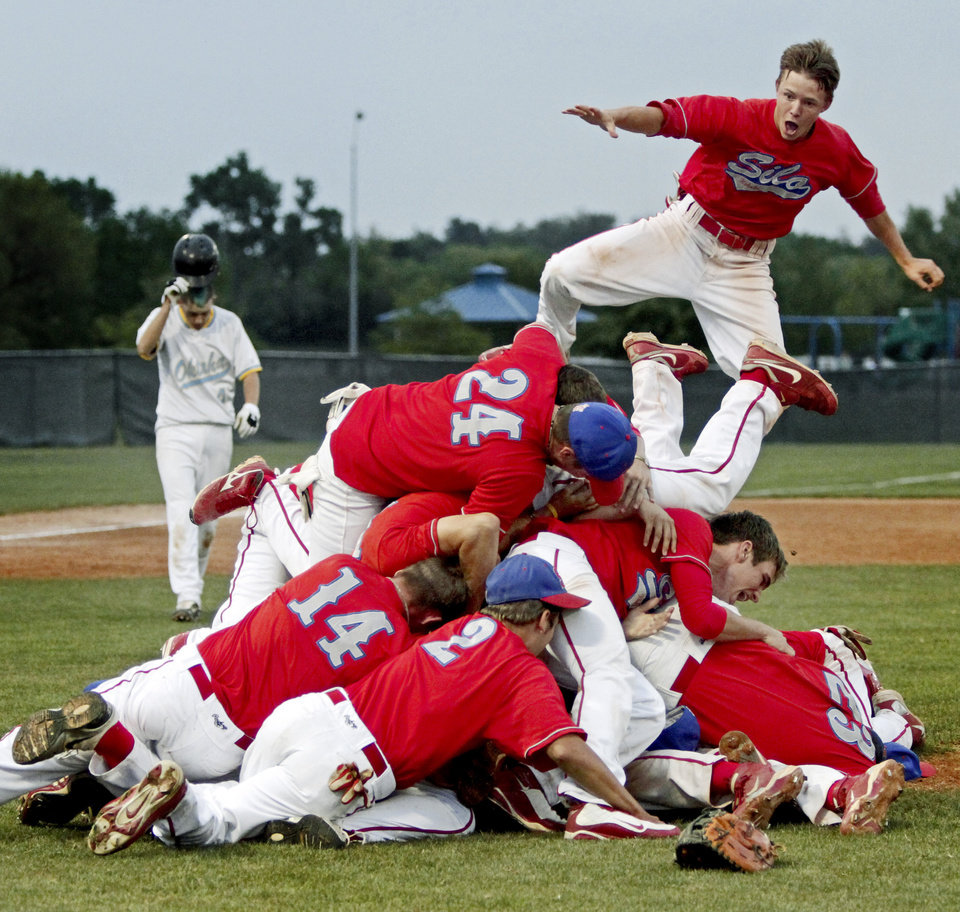 The Silo baseball team including B.W. Savage, upper right, celebrates as Oktaha's Derrick Skinner walks off the field following Silo's win in the Class 2A state baseball championship in Oklahoma City, Saturday, May 15, 2010. Photo by Bryan Terry, The Oklahoman