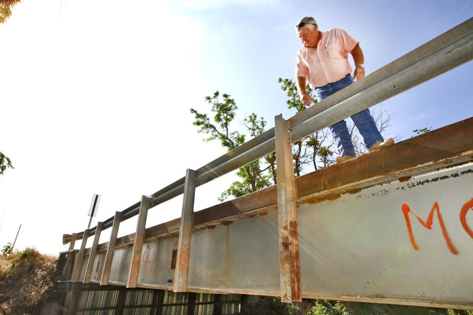 Photo - McClain County District 2 Commissioner Wilson Lyles stands on a bridge near Washington, OK, that was built with steel beams from the old Interstate 40 Crosstown Expressway.   David McDaniel - THE OKLAHOMAN