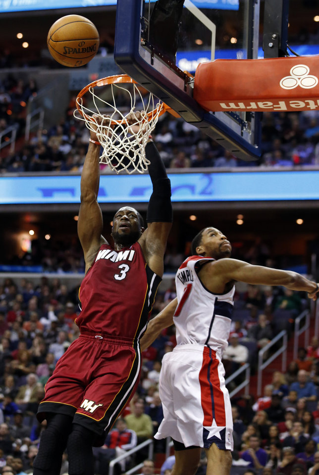 Photo - Miami Heat guard Dwyane Wade (3) misses a dunk in front of Washington Wizards guard Garrett Temple (17) in the first half of an NBA basketball game on Wednesday, Jan. 15, 2014, in Washington. (AP Photo/Alex Brandon)