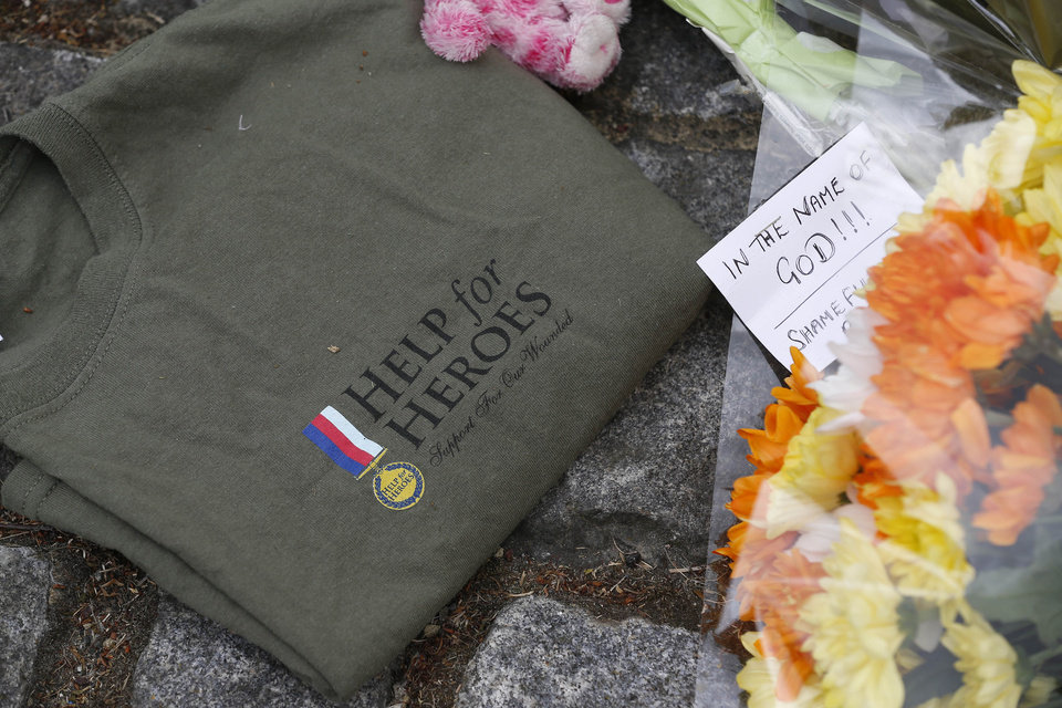Photo - A 'Help for Heroes' T-shirt and floral tributes in memory of the victim lay on the pavement outside the Royal Artillery Barracks near the scene of a terror attack in Woolwich, southeast London, Thursday, May 23, 2013. The British government's emergency committee met Thursday after two attackers killed a man in a daylight attack in London that raised fears terrorism had returned to the capital. (AP Photo/Sang Tan)