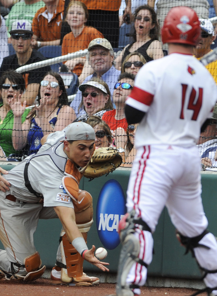 Photo - Texas catcher Tres Barrera, left, reaches for but does not catch a foul ball hit by Louisville's Kyle Gibson (14) in the fifth inning of an NCAA baseball College World Series elimination game in Omaha, Neb., Monday, June 16, 2014. (AP Photo/Eric Francis)