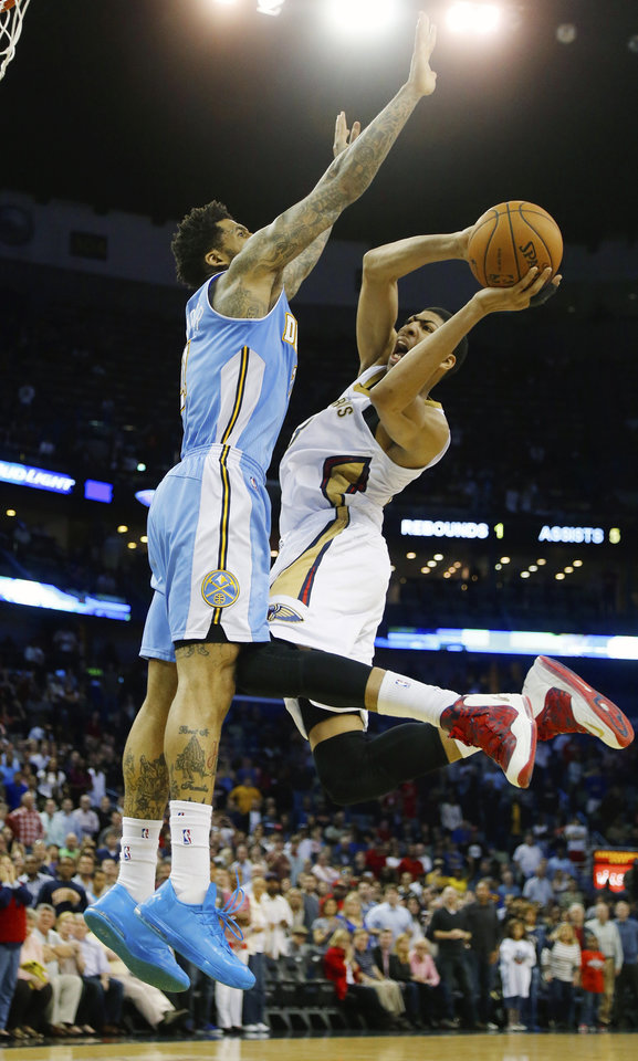 Photo - New Orleans Pelicans power forward Anthony Davis (23) shoots around Denver Nuggets small forward Wilson Chandler (21) in overtime in an NBA basketball game in New Orleans, Sunday, March 9, 2014. The Pelicans defeated the Nuggets 111-107. (AP Photo/Bill Haber)