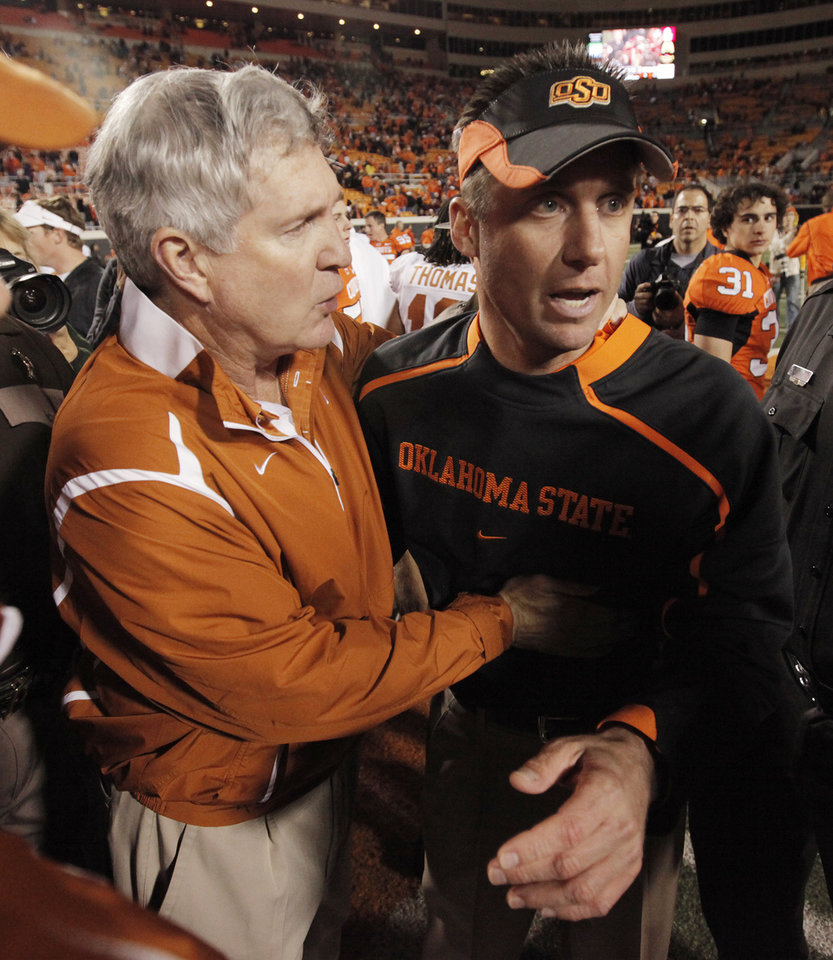 Photo - Texas head coach Mack Brown, left, talks with OSU head coach Mike Gundy after the college football game between the Oklahoma State University Cowboys (OSU) and the University of Texas Longhorns (UT) at Boone Pickens Stadium in Stillwater, Okla., Saturday, Oct. 31, 2009. Texas won, 41-14. Photo by Nate Billings, The Oklahoman