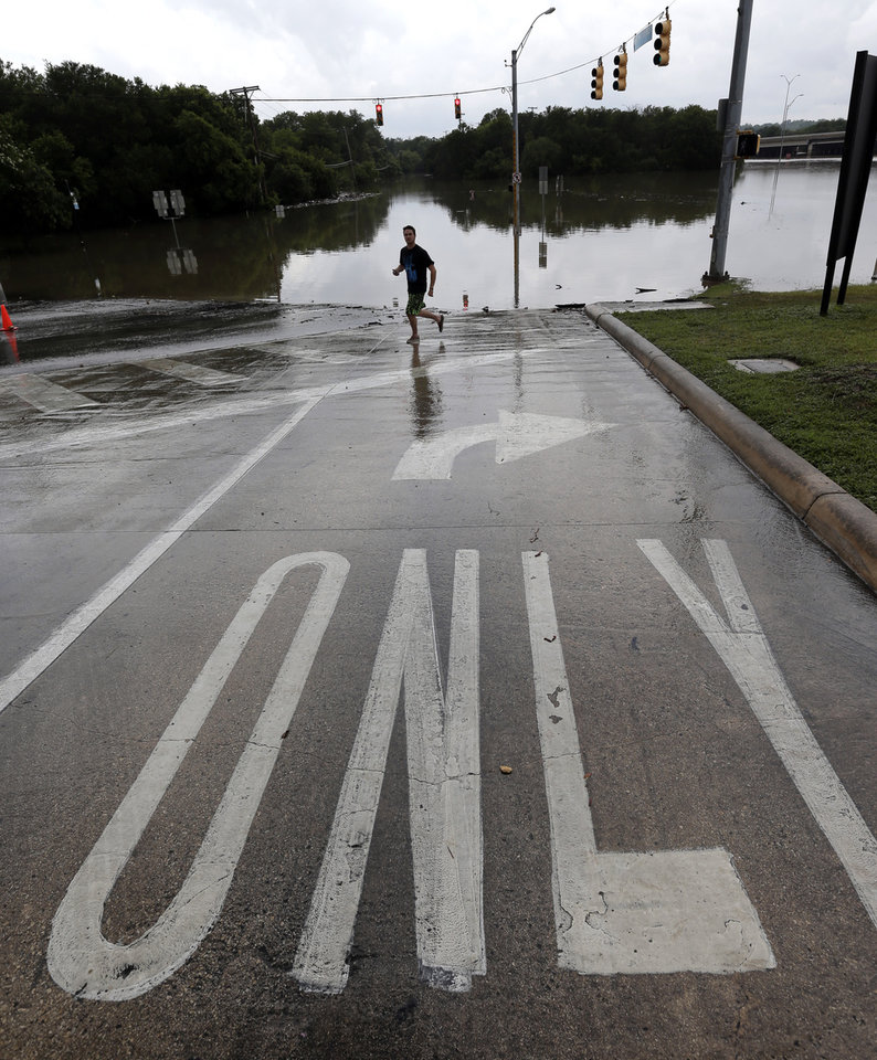Photo - An onlooker passes along a flooded intersection, Sunday, May 26, 2013, in San Antonio. Heavy rains and flooding are being blamed for at least two deaths in San Antonio. (AP Photo/Eric Gay)