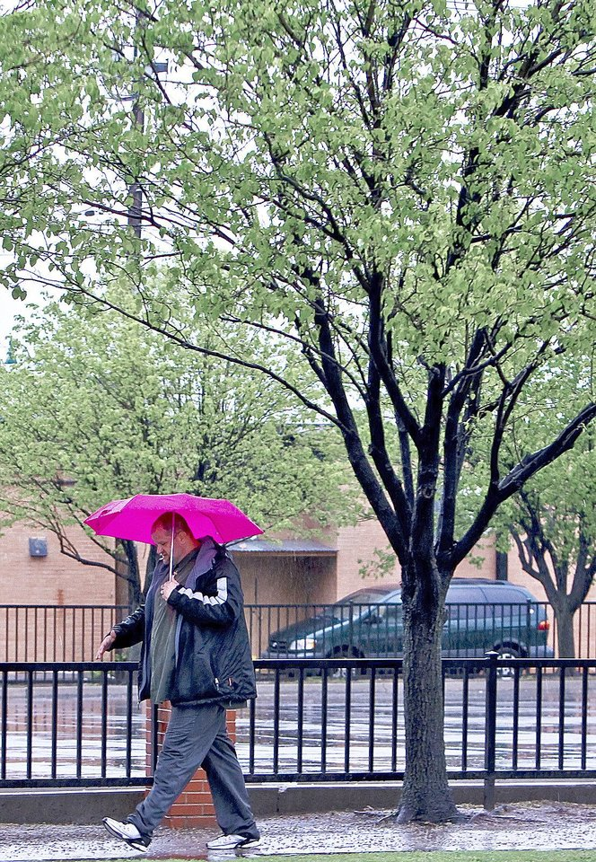 Photo - A pedestrian tries to stay dry under an umbrella  Monday while walking down  an Oklahoma City street as heavy rains fall.  Photos by Chris Landsberger, The Oklahoman