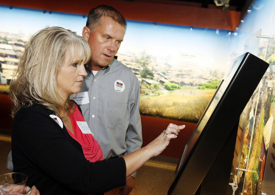 Photo - Joni Peters and Van Peters take an interactive quiz on poverty during the opening of the
