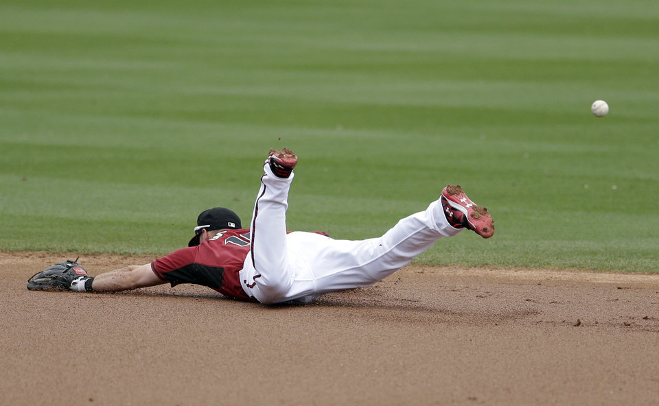 Photo - Arizona Diamondbacks shortstop Chris Owings can't reach a hit for a single by Oakland Athletics' John Jaso during the first inning of an exhibition spring training baseball game Thursday, March 6, 2014, in Scottsdale, Ariz. (AP Photo/Gregory Bull)