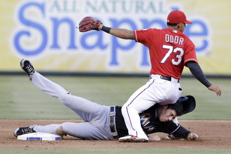 Photo - Texas Rangers second baseman Rougned Odor (73) lands on Miami Marlins Christian Yelich at second base turning a double play during the third inning of a baseball game in Arlington, Texas, Wednesday, June 11, 2014. Marlins Ed Lucas was out at first. (AP Photo/LM Otero)