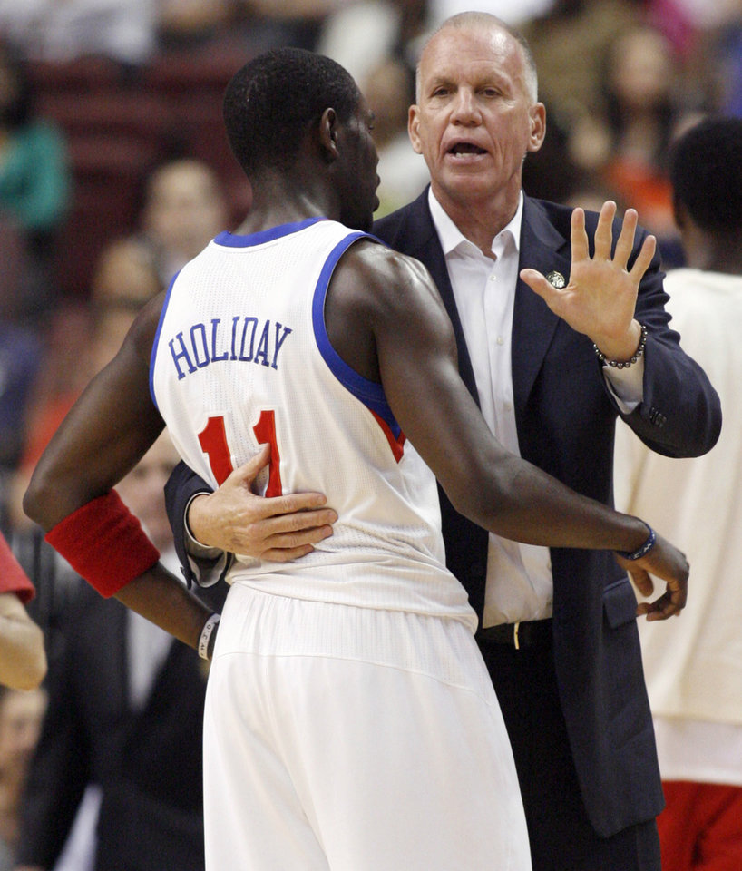 Photo - Philadelphia 76ers' Jrue Holiday (11) talks to 76ers coach Doug Collins during a time out against the Atlanta Hawks in the first half of an NBA basketball game, Wednesday, April 10, 2013, in Philadelphia. (AP Photo/H. Rumph Jr)