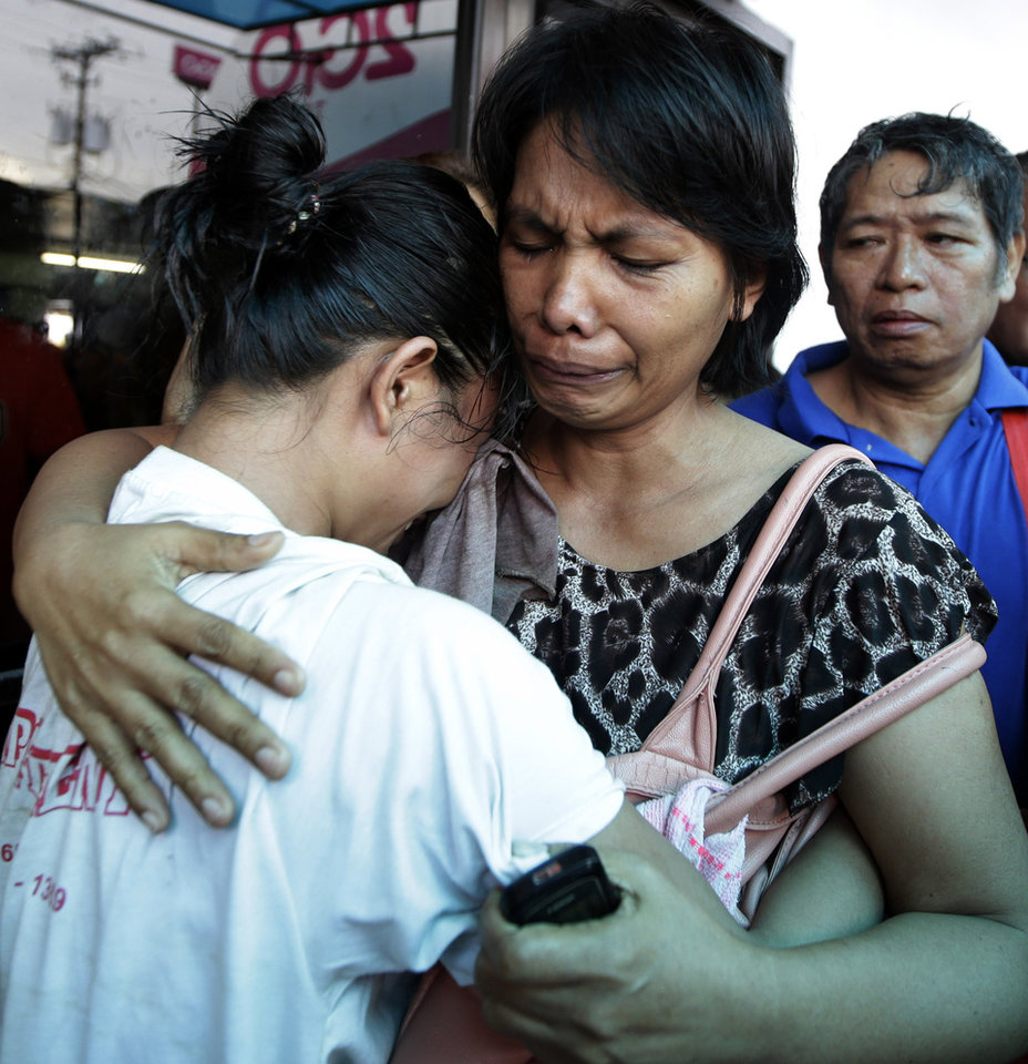 Photo - A survivor, left, of the ill-fated passenger ferry MV Thomas Aquinas, is comforted by a relative outside the ticketing office of a shipping company, Saturday Aug. 17, 2013, a day after the ferry collided with a cargo ship, the MV Sulpicio Express Siete, off the waters of Talisay city, Cebu province in central Philippines. Divers combed through the sunken ferry Saturday in search of dozens of people missing after the collision that sent passengers jumping into the ocean and leaving many others trapped. At least 31 were confirmed dead and hundreds rescued. (AP Photo/Bullit Marquez)