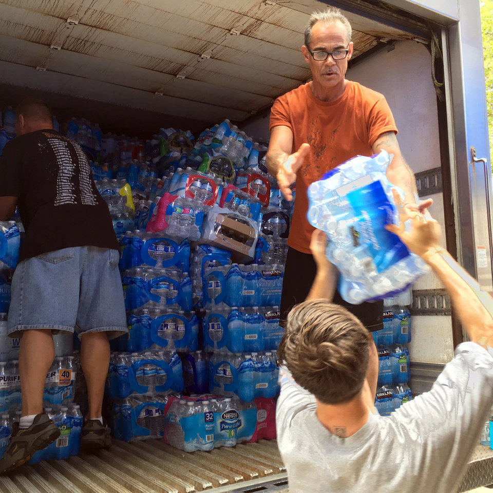 Photo - Volunteers load donated bottled water onto a truck for delivery to Philadelphia law enforcement officers providing security during the Democratic National Convention, on Monday, July 25, 2016, at the Cleveland Police Patrolmen's Association union hall in Cleveland. The union, with the help of local businesses, is sending two refrigerated trucks of water, sports drinks and Cleveland's famed corned beef sandwiches to Philadelphia law enforcement officers providing security during the Democratic National Convention in that city. (AP Photo/Mark Gillispie)