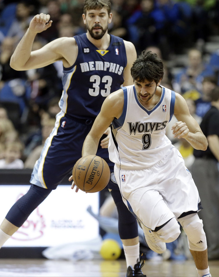 Photo - Minnesota Timberwolves' Ricky Rubio, right, of Spain, reaches the loose ball in time to beat Memphis Grizzlies' Marc Gasol, also of Spain, to the ball in the first quarter of an NBA basketball game on Saturday, March 30, 2013, in Minneapolis. (AP Photo/Jim Mone)