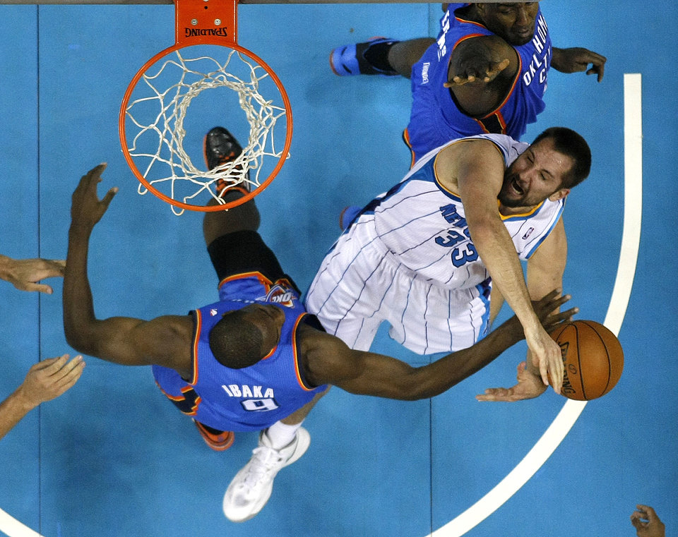 Photo - New Orleans Hornets forward Ryan Anderson (33) is blocked as he goes to the basket by Oklahoma City Thunder  forward Serge Ibaka (9) and center Kendrick Perkins, top, in the first half of an NBA basketball game in New Orleans, Saturday, Dec. 1, 2012. (AP Photo/Gerald Herbert)