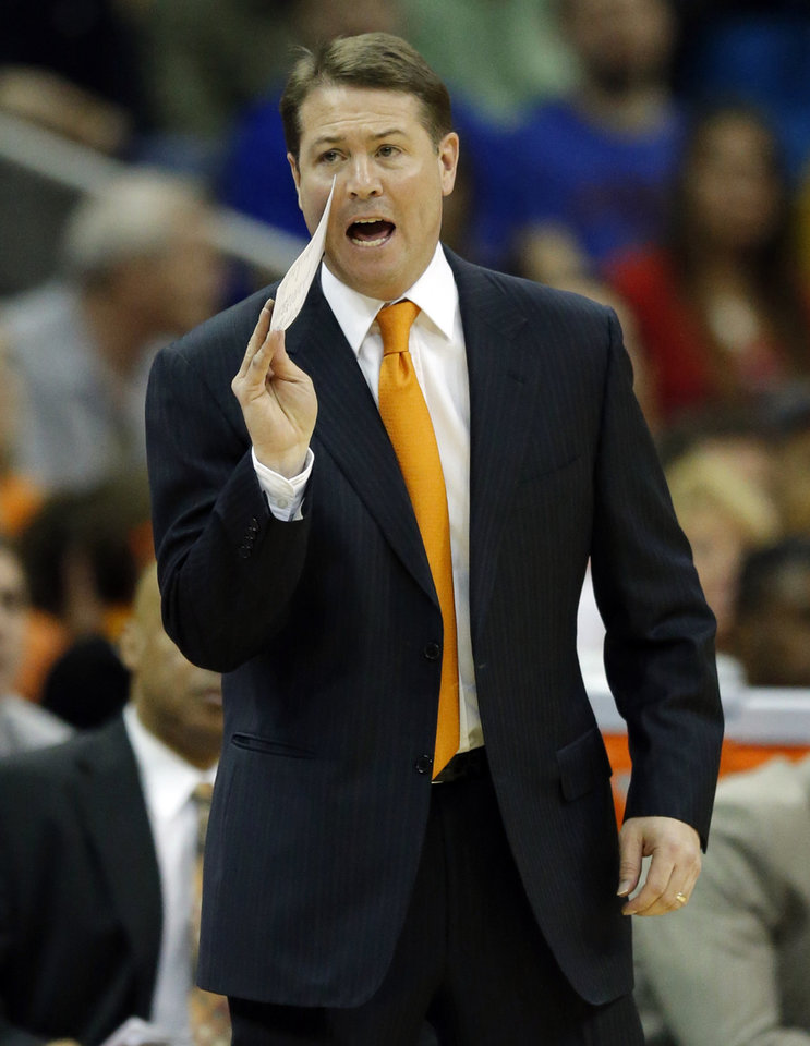 Photo - Oklahoma State head coach Travis Ford yells to his team during the first half of an NCAA college basketball game against Kansas in the quarterfinals of the Big 12 Conference men's tournament in Kansas City, Mo., Thursday, March 13, 2014. (AP Photo/Orlin Wagner)