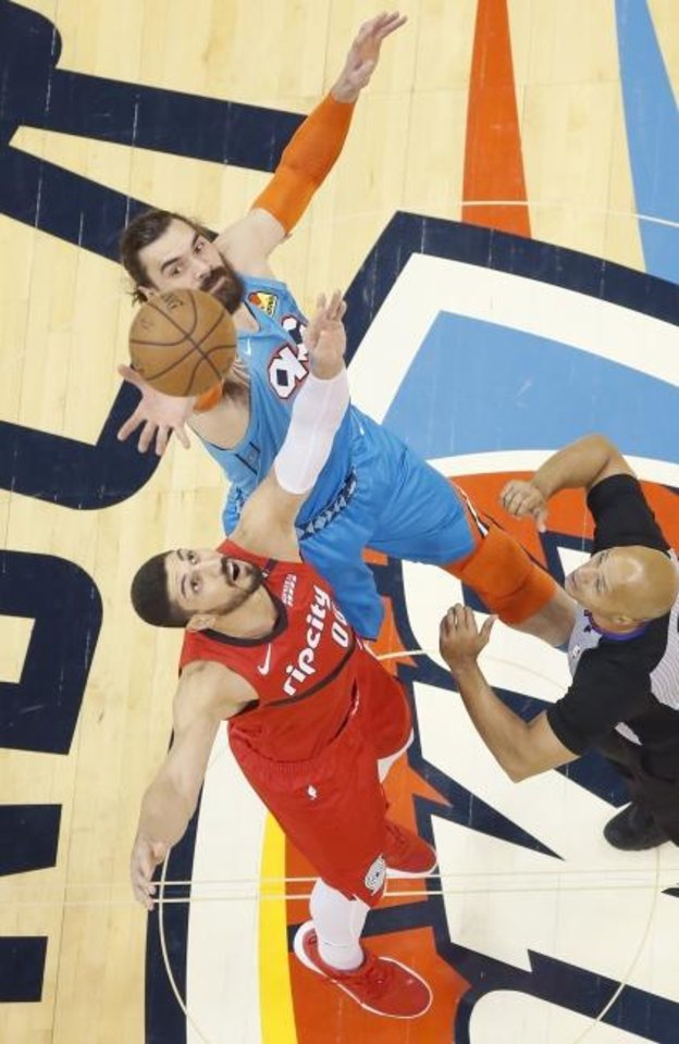 Photo -  Steven Adams (12) and Portland's Enes Kanter (00) jump for the ball during tip-off of Game 3 in their playoff series. [Bryan Terry/The Oklahoman]