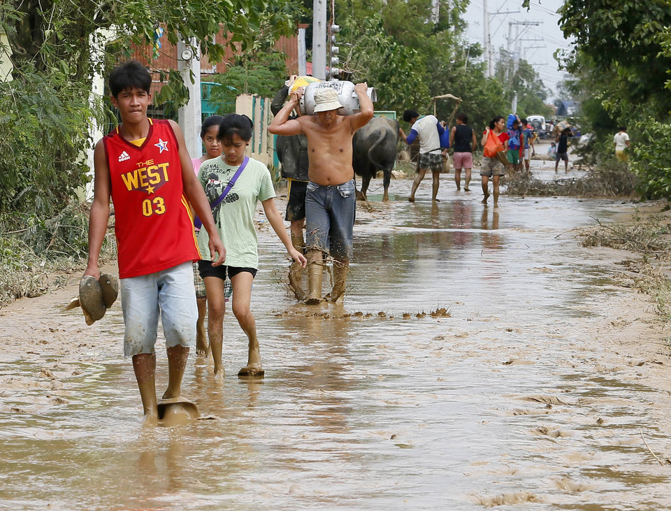 Photo - Residents walk back to their homes with cooking gas tank and food stuff in Cabanatuan, northern Philippines, Tuesday, Oct. 20, 2015, two days after Typhoon Koppu flooded Cabanatuan city and nearby provinces. Slow-moving Typhoon Koppu blew ashore with fierce wind in the northeastern Philippines early Sunday, toppling trees and knocking out power and communications and forcing the evacuation of thousands of villagers. (AP Photo/Bullit Marquez)