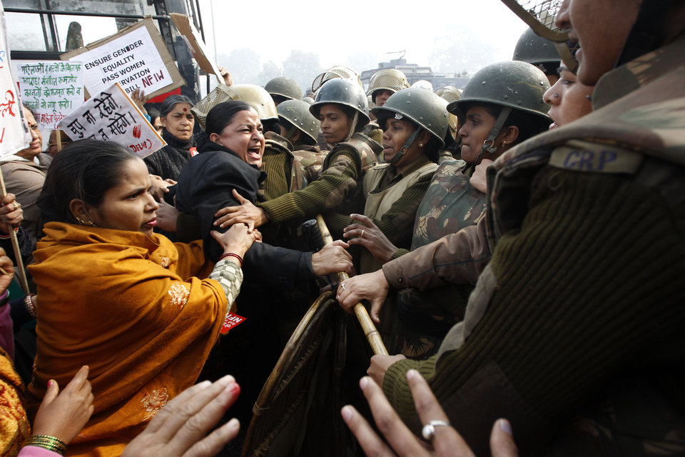 Indian police try to stop women protesters demonstrating against a gang rape and brutal beating of a 23-year-old student on a bus in New Delhi, India, Sunday, Dec. 23, 2012. The attack last Sunday has sparked days of protests across the country. (AP Photo/Tsering Topgyal)