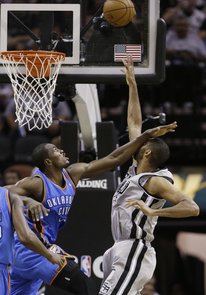 San Antonio Spurs' Tim Duncan, rifght, is hit in the face by Oklahoma Thunder's Serge Ibaka, left, as he shoots during the third quarter of an NBA basketball game, Thursday, Nov. 1, 2012, in San Antonio. (AP Photo/Eric Gay) ORG XMIT: TXEG113
