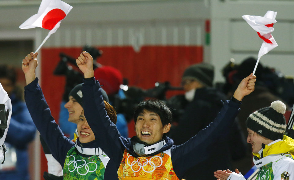 Photo - Japan's Taku Takeuchi, left, and Daiki Ito celebrate winning the bronze as Germany's Marinus Kraus, right, applauds after  the ski jumping large hill team competition at the 2014 Winter Olympics, Monday, Feb. 17, 2014, in Krasnaya Polyana, Russia. (AP Photo/Dmitry Lovetsky)