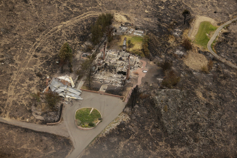 Photo - This aerial photo shows structures which were destroyed by wildfires near Pateros, Wash. on Thursday, July 24, 2014. Fire spokesman Pete Buist says the biggest wildfire in the state's history remains at 52 percent contained on Thursday. However, the weather forecast calls for hot and dry conditions to return over the next few days. (AP Photo)