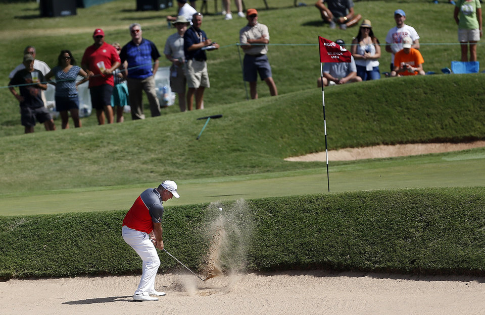 Photo - Hendrick Buhrmann hits out of the sand on the 8th hole in the third round of the U.S. Senior Open golf tournament at Oak Tree National in Edmond, Okla., Saturday, July 12, 2014. Photo by Sarah Phipps, The Oklahoman