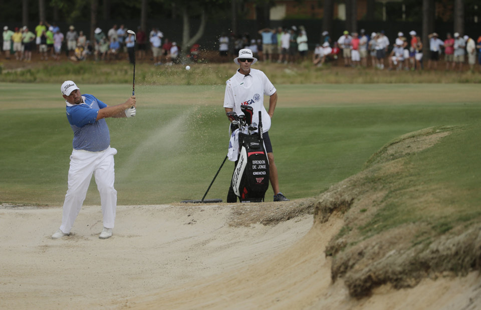 Photo - Brendon De Jonge, of Zimbabwe, hits out of the bunker on the seventh hole during the third round of the U.S. Open golf tournament in Pinehurst, N.C., Saturday, June 14, 2014. (AP Photo/Chuck Burton)