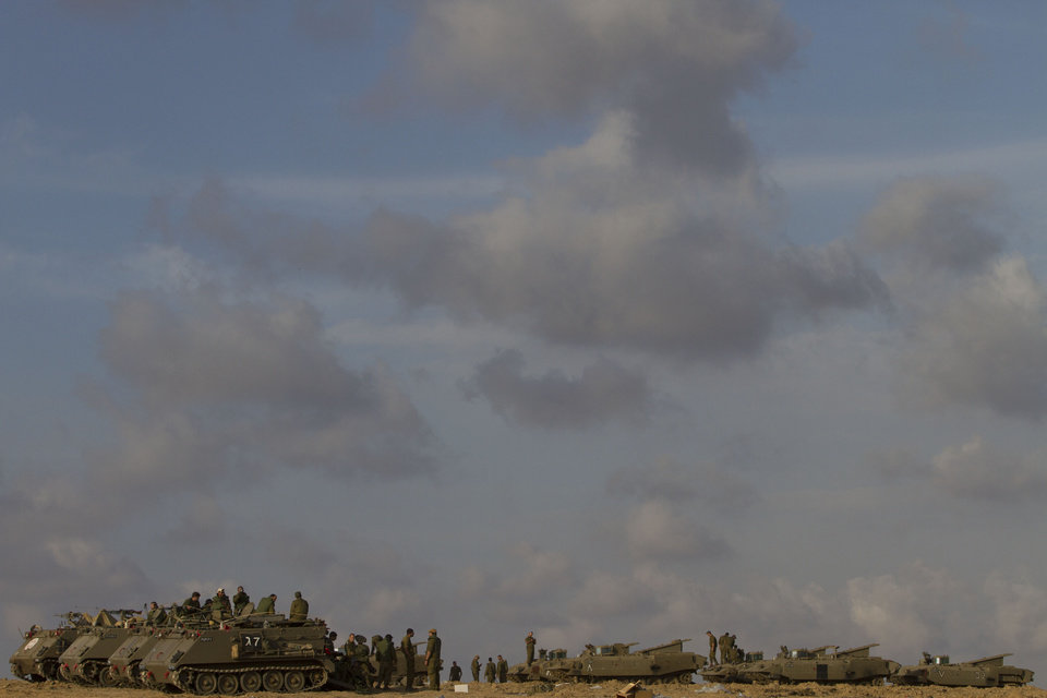 Israeli soldiers gather with their armored personnel carriers in a gathering area near the Israel Gaza Strip border, in southern Israel, Sunday, Nov. 18, 2012. President Barack Obama on Sunday defended Israel's airstrikes on the Gaza Strip, but he warned that escalating the offensive with Israeli ground troops could deepen the death toll and undermine any hope of a peace process with the Palestinians. (AP Photo/Ariel Schalit)