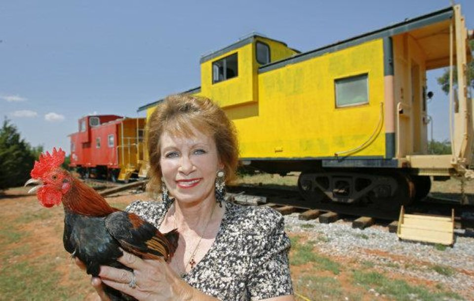 Debbie Morse holds a red rooster in front of two cabooses at her Red Rooster Inn on the Northwest Expressway in Canadian County, Thursday, August 24, 2006. BY DAVID MCDANIEL, THE OKLAHOMAN ORG XMIT: KOD DAVID MCDANIEL - THE OKLAHOMAN