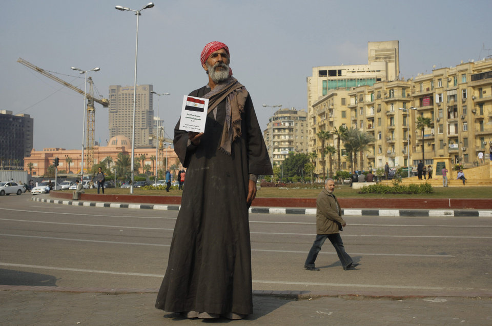 Photo - An Egyptian farmer holds a copy of the draft constitution in Tahrir Square, the focal point of Egyptian uprising, in Cairo, Egypt, Saturday, Jan. 11, 2014. The January 14-15 vote on the draft constitution will be the first real test since Mohammed Morsi was ousted from presidency. (AP Photo/Amr Nabil)