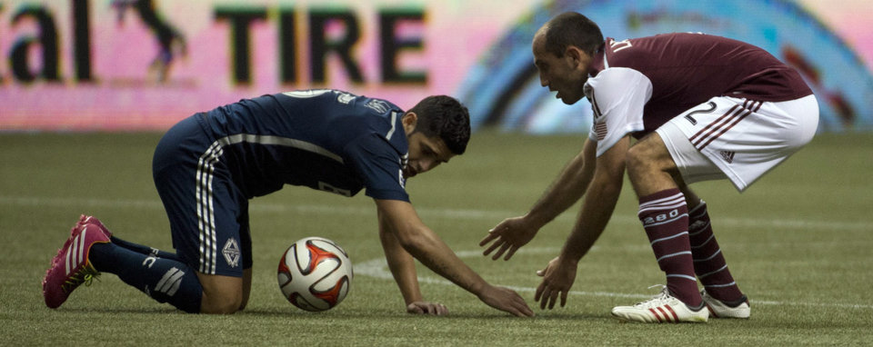 Photo - Vancouver Whitecaps FC's Matias Laba fights for control of the ball with Colorado Rapids FC's Nick LaBrocca during second half of MLS soccer action in Vancouver, Canada, Saturday, April 5, 2014. (AP Photo/The Canadian Press, Jonathan Hayward)