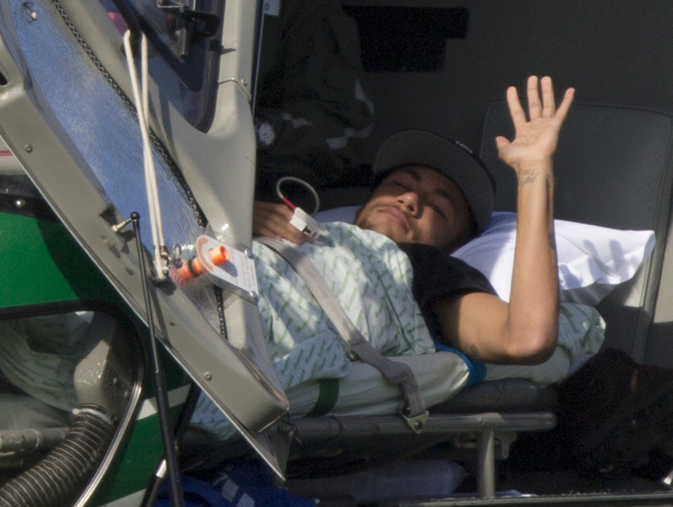 Photo - Brazil's Neymar waves as he lies inside a medical helicopter at the Granja Comary training center, in Teresopolis, Brazil, Saturday, July 5, 2014. Neymar was airlifted from Brazil's training camp Saturday and will be treated at home for his back injury. Neymar, the biggest football star in Brazil, was ruled out of the rest of the World Cup after fracturing his third vertebra during Friday's 2-1 quarterfinal win over Colombia. (AP Photo/Leo Correa)
