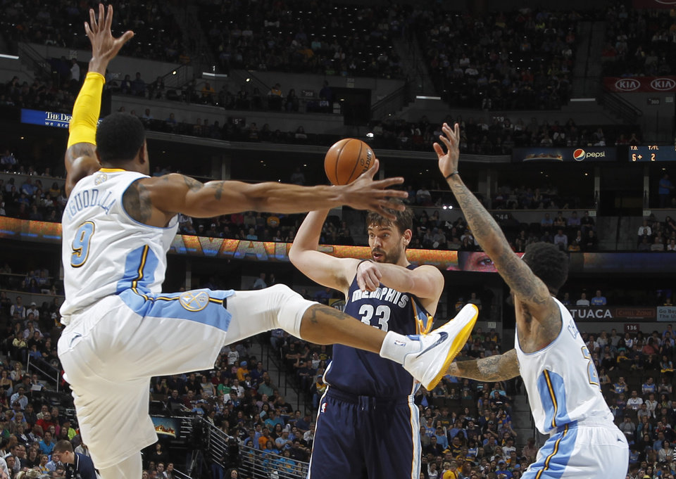 Photo - Memphis Grizzlies center Marc Gasol, center, of Spain, looks to pass the ball under pressure from Denver Nuggets guard Andre Iguodala, front left, and forward Wilson Chandler in the first quarter of an NBA basketball game in Denver, Friday, March 15, 2013. (AP Photo/David Zalubowski)
