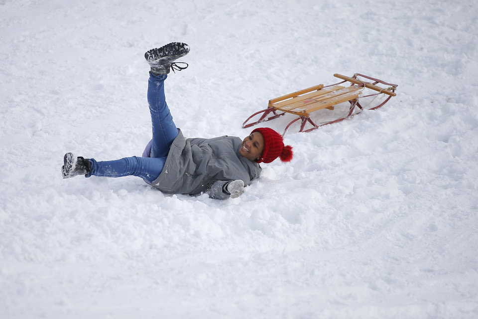Photo - Jaleesa Daniels, 13, falls off her sled on a hill along W Hefner Road in Oklahoma City after a winter storm dropped another layer of snow in Oklahoma City, Wednesday, Feb. 17, 2021. [Bryan Terry/The Oklahoman]