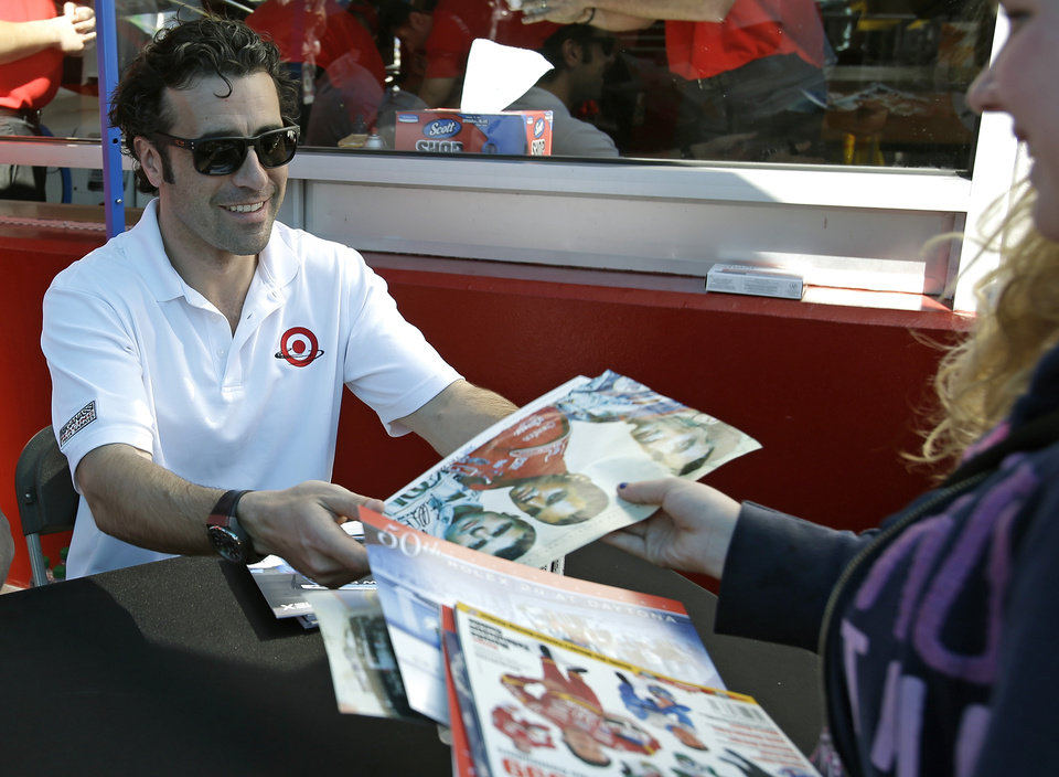 Photo - Dario Franchitti, of Scotland, hands a signed poster to a race fan in the garage area prior to the start of the Grand-Am Series Rolex 24 hour auto race at Daytona International Speedway, Saturday, Jan. 26, 2013, in Daytona Beach, Fla. (AP Photo/John Raoux)