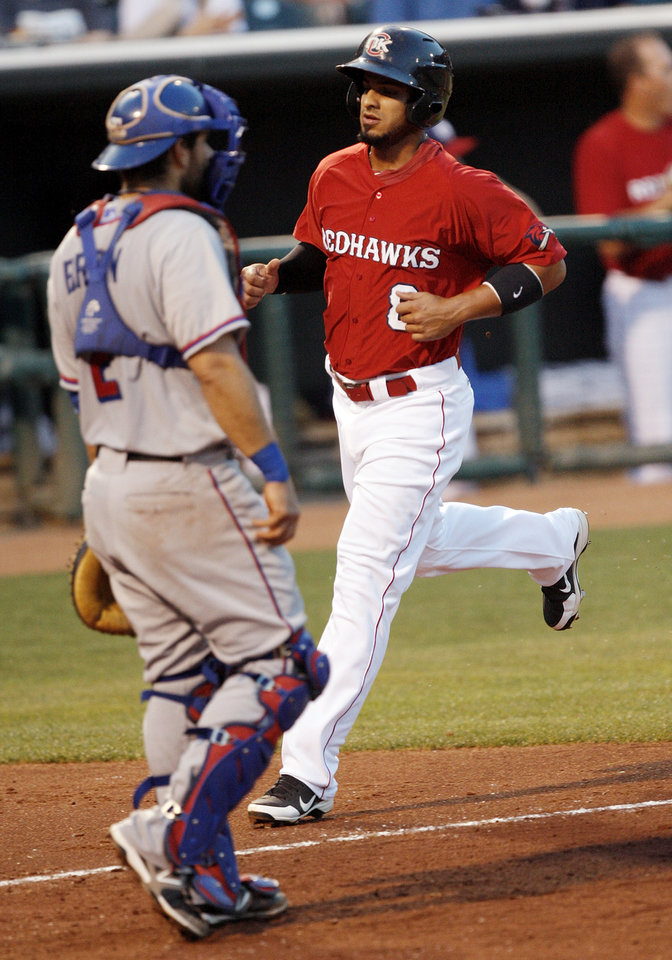 Photo - Oklahoma City's Fernando Martinez (8) runs home to score past Round Rock catcher Dusty Brown (2) in the third inning during a minor league baseball game between the Oklahoma City RedHawks and the Round Rock Express at Chickasaw Bricktown Ballpark in Oklahoma City, Thursday, April 26, 2012. Photo by Nate Billings, The Oklahoman